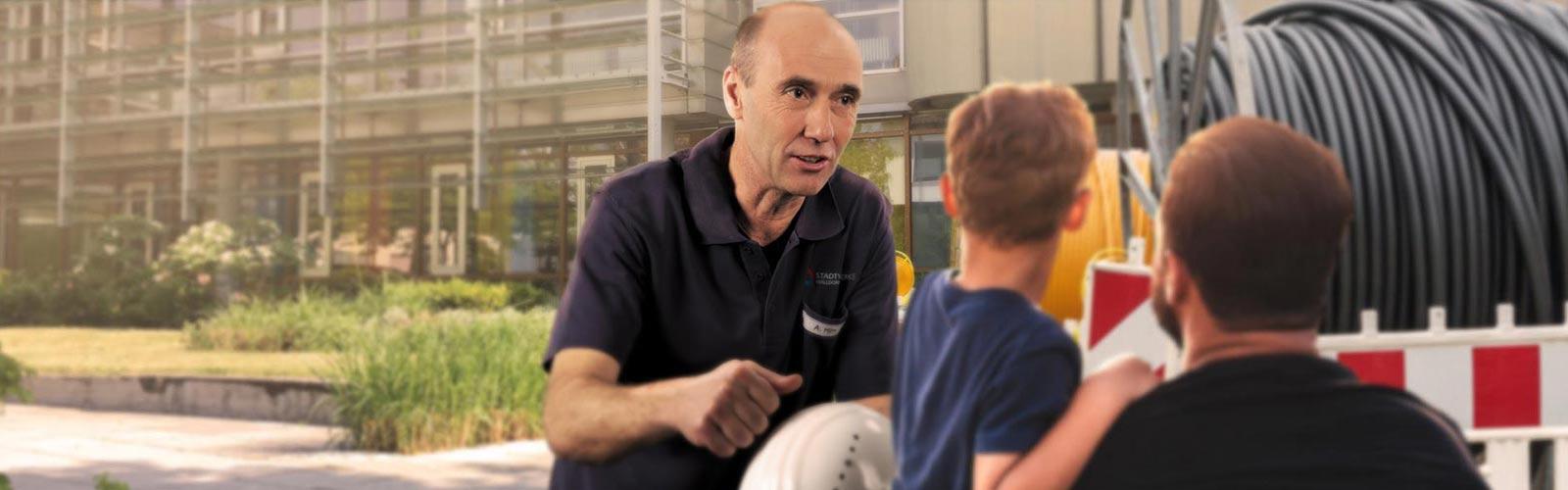 Andreas Hirn von den Stadtwerken Walldorf erklärt einem Vater mit seinem Sohn das Verlegen der neuen Leitungen.